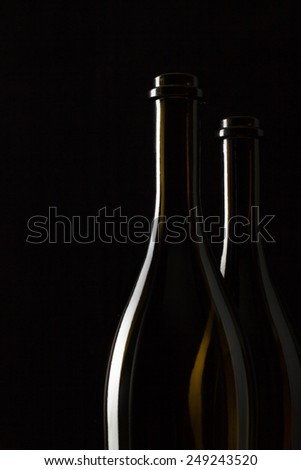 Silhouettes of elegant wine bottles on a black background