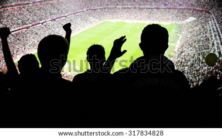 Silhouettes of fans celebrating a goal on football match - stock photo