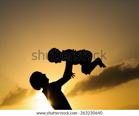 silhouettes of father and little son playing at sunset - stock photo
