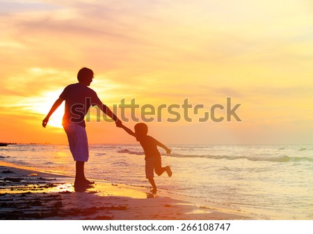 silhouettes of father and son having fun on sunset beach