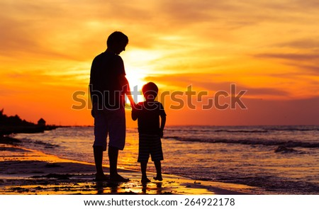 silhouettes of father and son holding hands at sunset sea - stock photo