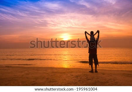 silhouettes of father and son on sunrise sea background,family concept - stock photo