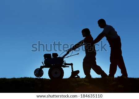 Silhouettes of father and son working the land with a tiller - small scale organic farming concept - stock photo