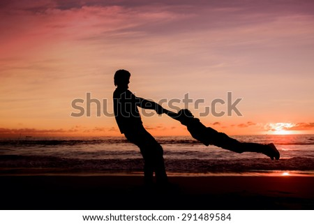 Silhouettes of father spinning his son around on sunset on the beach having great family time together - stock photo