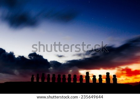 Silhouettes of fifteen moais against starry blue sky in Easter Island, Chile - stock photo