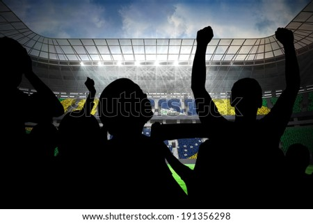 Silhouettes of football supporters against large football stadium with brasilian fans - stock photo