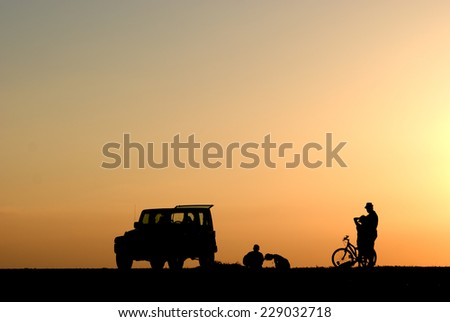Silhouettes of four people, cars and bicycle at sunset - stock photo