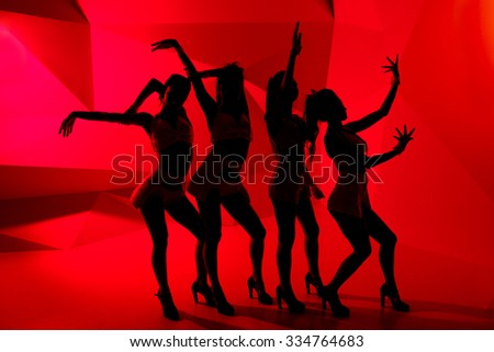 Silhouettes of four slim dancing girls