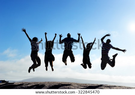 Silhouettes of group of friends jumping outdoors on a beach in unison with arms up - stock photo