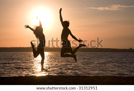 Silhouettes of happy couple jumping on background of lake at sunset - stock photo