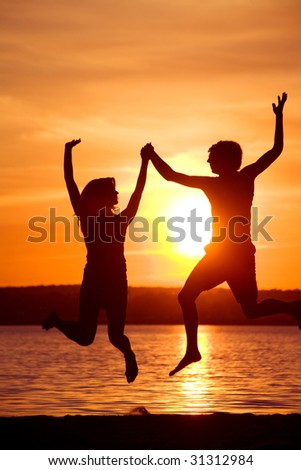 Silhouettes of happy couple jumping with raised arms near lake at sunset - stock photo