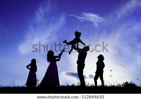 Silhouettes of happy parents having fun with their children - stock photo