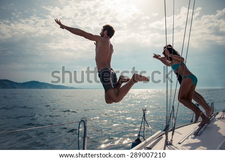 Silhouettes of happy people jumping into water from a boat - Friends diving and having fun on a summer vacation - stock photo