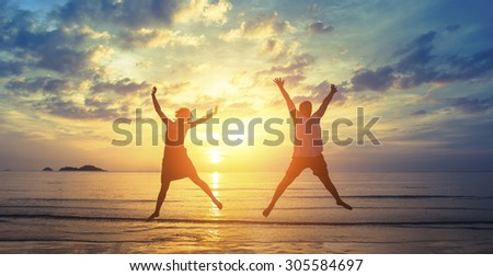 Silhouettes of happy young couple jumping on the ocean beach in the rays fantastic sunset.