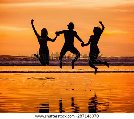 Silhouettes of happy young friends jumping on the beach  on sunset with beautiful red sky on background