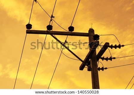 Silhouettes of High voltage pole and power lines on sunset - stock photo