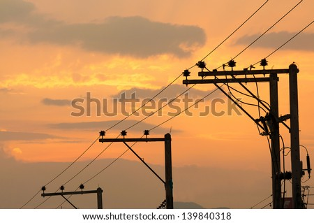 Silhouettes of High voltage poles and power lines on sunset - stock photo