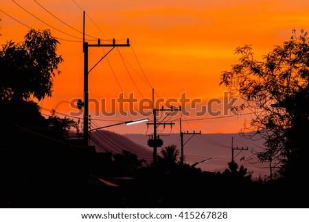 silhouettes of high voltage power lines on sunset