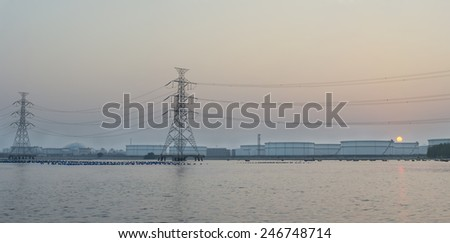 Silhouettes of High-voltage tower and large white tanks for petrol and oil - stock photo
