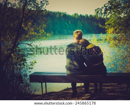 Silhouettes of hugging couple sitting on bench against the lake at sunset. Vintage photo. - stock photo