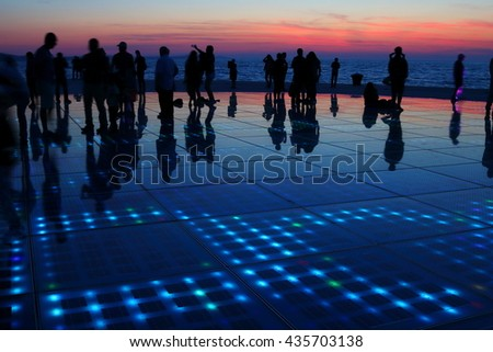 Silhouettes of humans in various activities upon a sunset background, with reflections on solar panels on the ground, forming a beautiful human symphony - stock photo