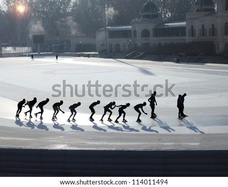 Silhouettes of ice skating people on ice - stock photo