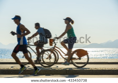 Silhouettes of joggers and cyclists sharing the bike path on the beachfront Avenida Atlântica street at Copacabana Beach in Rio de Janeiro, Brazil - stock photo