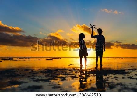 Silhouettes of kids brother and sister  holding starfish at tropical beach during sunset - stock photo