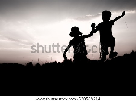 Silhouettes of kids jumping off a cliff at sunset. Boy and girl jump high holding hands. Brother and sister having fun in summer. Friendship, freedom concept. Vacation in mountains.