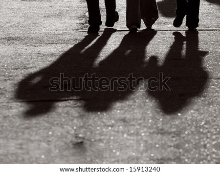 Silhouettes of legs of three walking friends