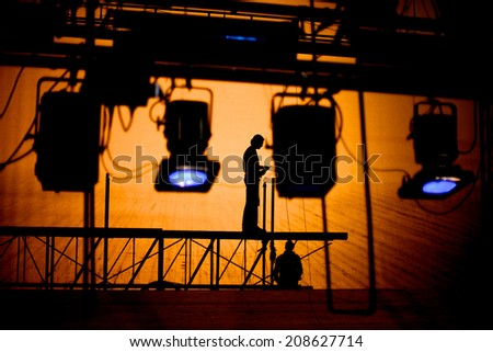 Silhouettes of lightening technicians standing on a scaffold regulating illumination of the stage - stock photo