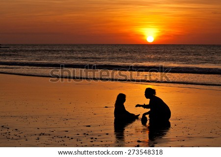 Silhouettes of little girl and mother at the beach during sunset in Manabi, Ecuador - stock photo