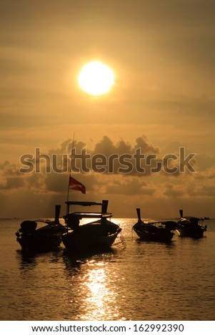 Silhouettes of longtail boats at sunrise - stock photo