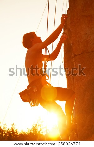 Silhouettes of  man climbing on a cliff at sunset - stock photo
