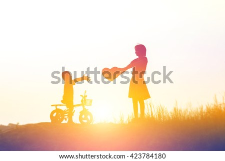 Silhouettes of mather and little daughter walking at sunset