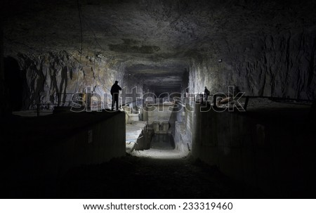 silhouettes of men in cave/ old mine  - stock photo