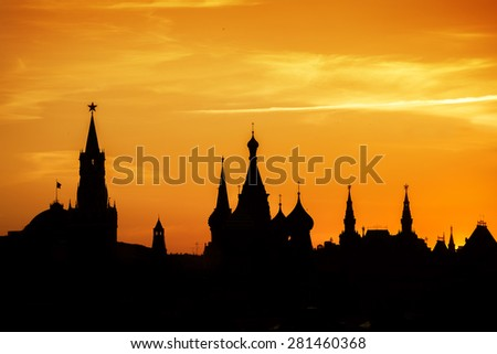 Silhouettes of Moscow Kremlin and St. Basil's Cathedral at Red square on sunset light  - stock photo