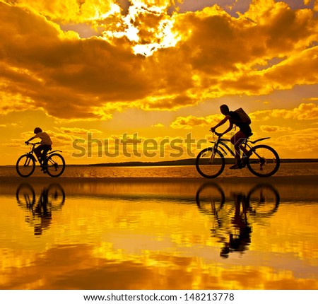 silhouettes of mother and child on bicycle against sunset sky With reflection on water Copy space for inscription  - stock photo