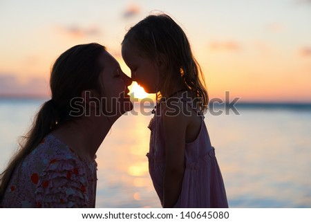Silhouettes of mother and daughter at sunset - stock photo