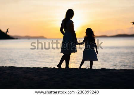 Silhouettes of mother and daughter walking along tropical beach during sunset - stock photo