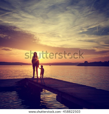 Silhouettes of Mother with Her Son by the Sea