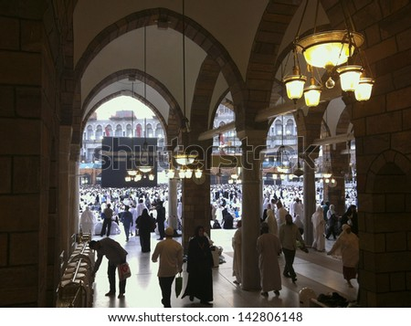Silhouettes of Muslim pilgrims circumambulate the Kaaba from ground floor of Haram Mosque in Mecca. Muslims all around the world face the Kaaba during prayer time. - stock photo
