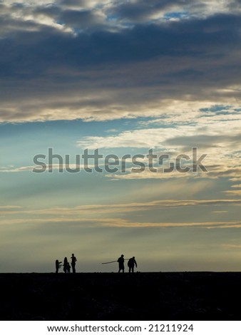 Silhouettes of mussel collectors at sunset in Veulettes sur Mer - Normandy - France - stock photo