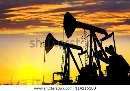 Silhouettes of oil pumps at dawn sky background - stock photo