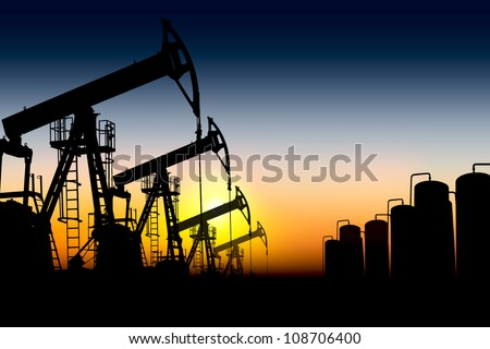 silhouettes of oil pumps placed one after another against the sunset - stock photo
