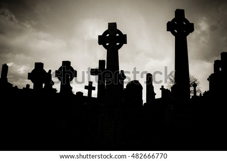 Silhouettes of Old stone celtic crosses on a graveyard. Artistic dramatic monochrome aged grainy edit with a strong vignette