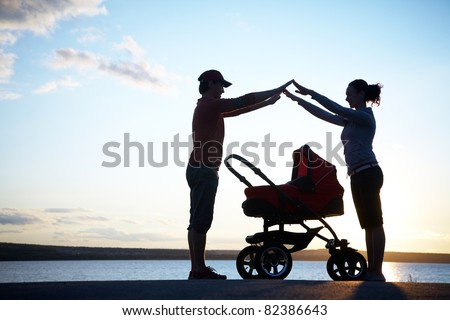 Silhouettes of parents protect their child in a stroller - stock photo