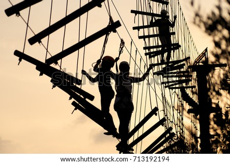Silhouettes of people a walking on a rope ladder, a rope park. Family hobby