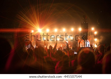 Silhouettes of people and musicians on big concert stage - stock photo