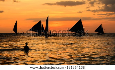 Silhouettes of people and sailing boats against an orange tropical sunset - stock photo